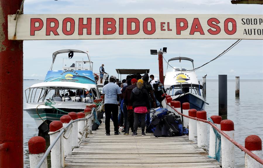 Migrantes de diversas partes del mundo suben a embarcaciones con destino a Capurganá, el 3 de mayo de 2021, en el embarcadero de Necoclí (Colombia).