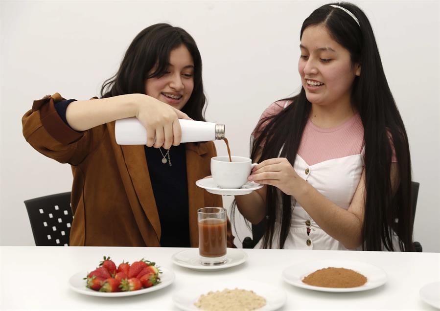 Las estudiantes Alexa Castañeda (d) y Esther Rivera de la Universidad de Ciencias y Artes de América Latina (UCAL) presentan una bebida preparada a base de grillos, el 29 de junio de 2021, en Lima (Perú).
