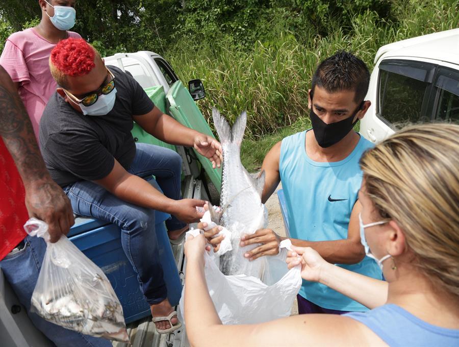 El pescador venezolano Carlos Hernández (i) regala bolsas de pescado a personas de familias necesitadas este domingo en St. Helena, Trinidad y Tobago.
