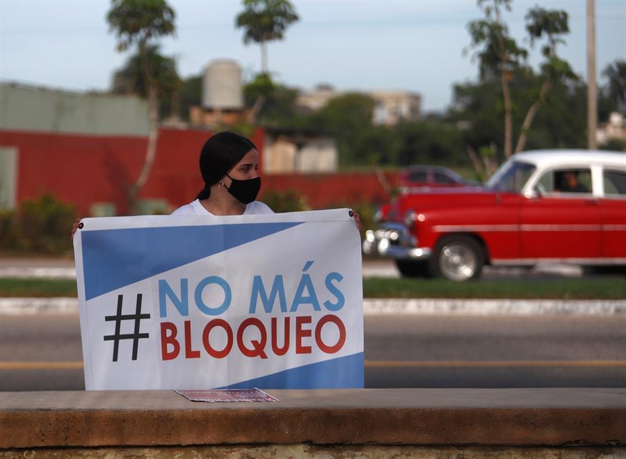 Fotografía del 20 de junio que muestra a una mujer que sostiene un cartel, durante la regata parte de una campaña contra el bloqueo de Estados Unidos a la isla, en la bahía de Matanzas (Cuba).