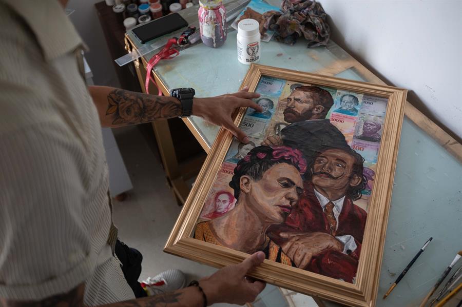 El artista venezolano Jeean Franco González enmarca una obra pintada sobre billetes de bolívares, el 8 de julio de 2021 en su estudio en Caracas (Venezuela).
