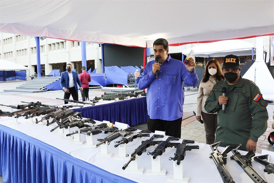 Fotografía cedida por el Palacio de Miraflores donde se observa al presidente de Venezuela Nicolás Maduro (c) mostrando parte del armamento incautado durante los operativos contra las bandas delictivas durante una alocución en Caracas (Venezuela).