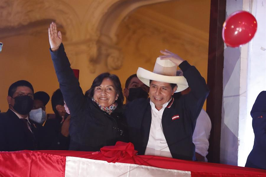 """El izquierdista Pedro Castillo (d), acompañado de su formula a la Vicepresidencia Dina Boluarte, saluda simpatizantes desde un balcón luego de ser proclamado hoy presidente electo del país, en Lima (Perú). La proclamación oficial se da este lunes, mes y medio después de los comicios en los que venció a la derechista Keiko Fujimori, quien retrasó su nombramiento con más de un millar de impugnaciones en las que denuncia sin pruebas fehacientes un supuesto """"fraude""""."""