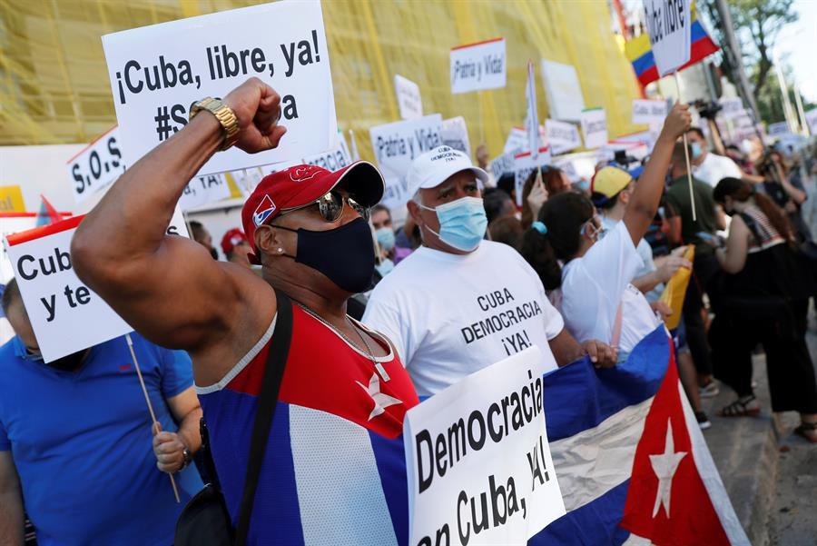 """Varias personas participan en la concentración """"Por una Cuba libre"""" frente a la embajada de Cuba en Madrid."""