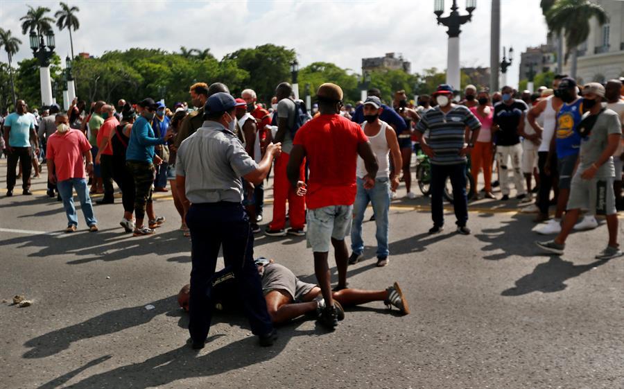 """Un hombre permanece en suelo antes de ser arrestado en La Habana (Cuba). Cientos de cubanos salieron este domingo a las calles de La Habana al grito de """"libertad"""" en manifestaciones pacíficas, que fueron interceptadas por las fuerzas de seguridad y brigadas de partidarios del Gobierno, produciéndose enfrentamientos violentos y arrestos."""