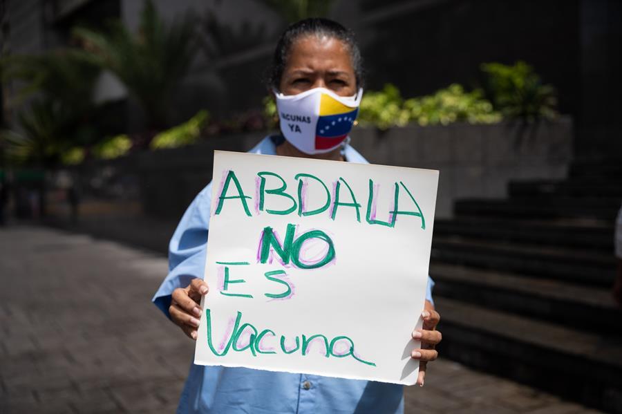 """Una persona con una pancarta participa en una protesta contra la vacuna cubana Abdala hoy, frente a la sede del Programa de las Naciones Unidas para el Desarrollo (PNUD), en Caracas (Venezuela). El Colegio de Enfermeros de Caracas y varios docentes reclamaron este viernes que no se aplique a menores de edad en Venezuela la vacuna cubana Abdala, que consideran que es todavía un """"prototipo"""" pese a haber recibido su autorización para el uso de emergencia por las autoridades de la isla."""