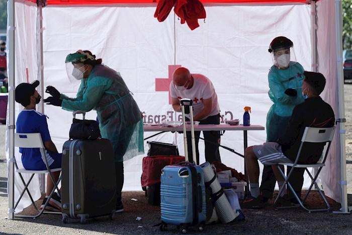 Varios trabajadores de Cruz Roja realizan una prueba PCR a un joven este jueves en Valladolid, momentos antes de subir al autobús que le lleva a un campamento de verano.