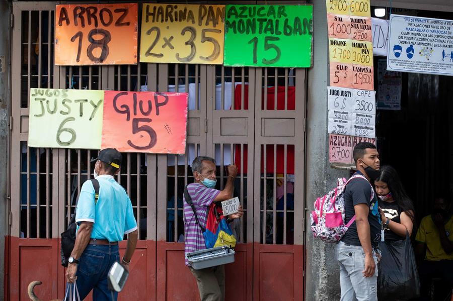 Varias personas esperan frente a un supermercado el 25 de junio de 2021, en Caracas (Venezuela). Venezuela lleva inmersa en la pesadilla de la hiperinflación desde noviembre de 2017, una época de cifras mareantes que ha derivado en una dolarización espontánea como boya de salvación. Sin embargo, en los últimos meses, el incremento de los precios ha comenzado a frenarse, lo que alimenta la esperanza de dejar atrás el mal sueño.